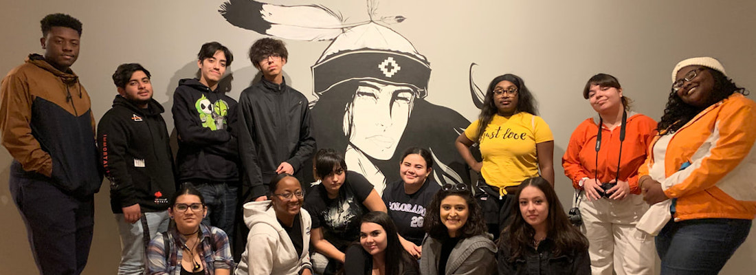 Students posing in a group in front of a mural